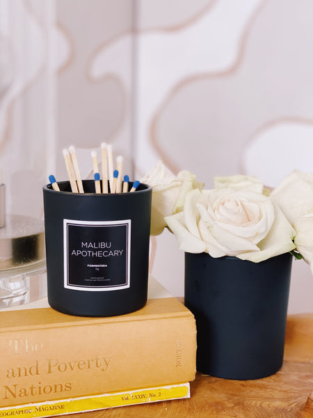 Repurposing a candle vessel for matches and as a flower vase on a coffee table