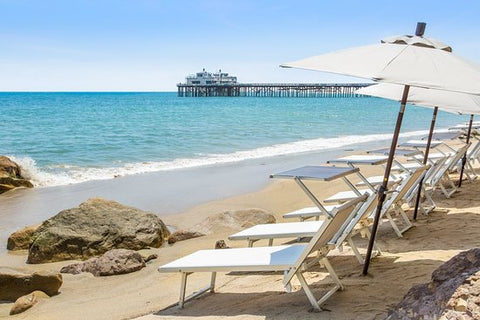 Row of beach chairs and umbrellas on the sand facing the ocean in Malibu Beach, California with the pier in the background
