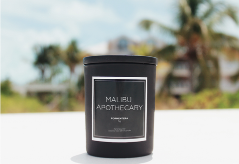 Scented Matte Black candle sitting on the beach in front of palm trees and ocean in Turks & Caicos