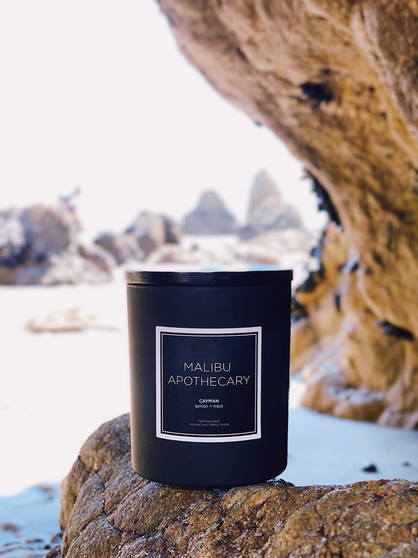 A Matte Black Candle at the beach in Malibu, California sitting on a rock in the Abaco, Bahamas scent with notes of red currant, grapefruit, and lemon