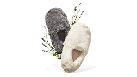 one grey and one ivory fuzzy slipper with sprigs of lavender behind them