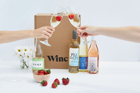 """two hands clinking champagne glasses, with bottles of wine, strawberries and flowers sitting in front of a box labeled """"Winc"""""""