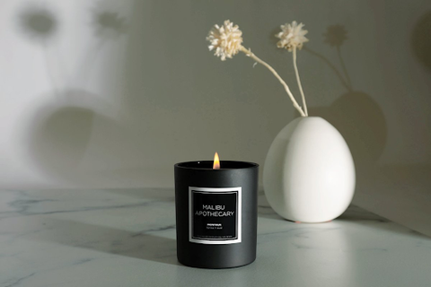 Malibu Apothecary Matte Black candle with a round, white vase behind it with two tan flowers