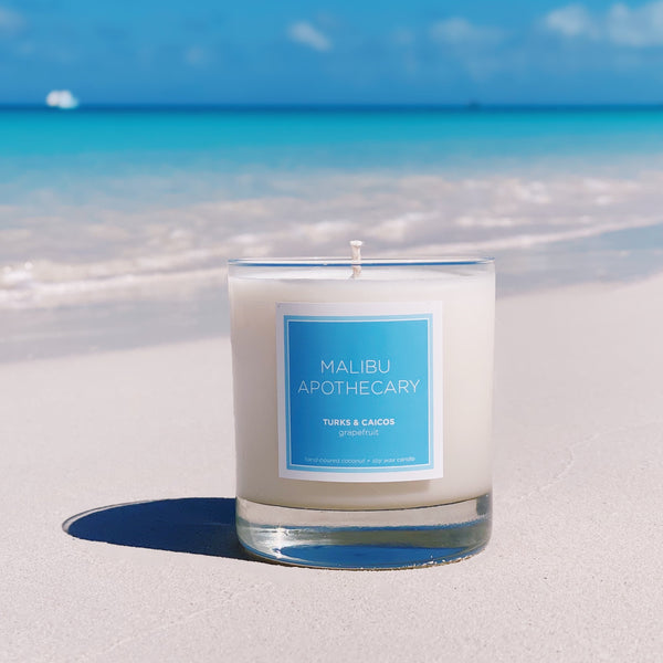 Malibu Apothecary Candle in Clear Gloss and Blue label on the sand in front of the waves in Turks & Caicos