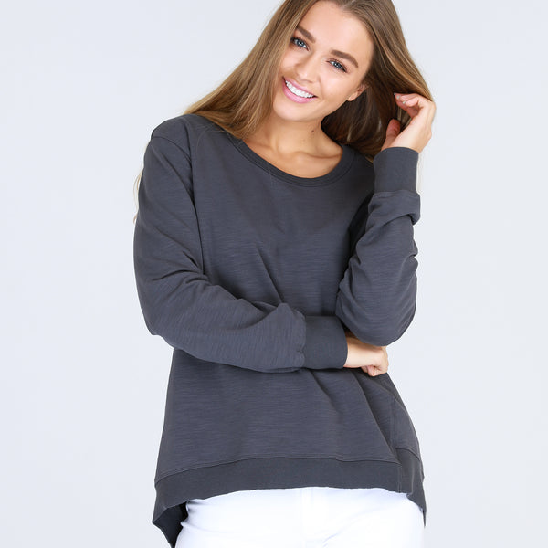 The Newhaven Sweater is a relaxed, mid-weight sweater that features an asymmetrical hemline that dips at the back on one side, as a stylish point of difference.  This will become your new favourite sweat to wear on a casual weekend, to the gym and when travelling.  Designed for an oversized look.  FEATURES Round neckline Hi-Lo hemline – shorter at the front, dipping longer to one side at the back Relaxed fit Ribbed edging FABRIC 100% Cotton Warm machine wash