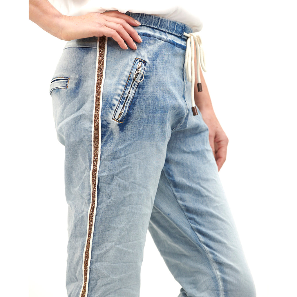 These super stretchy, faded denim jeans are both cool and comfortable.  With an ankle length leg, zip pockets and lurex ribbon detail, we know you will be living in the gold trim jogger all-year-round.  FEATURES • Elasticised waist • Lurex ribbon detail • Drawstring tie • Faded look • Ankle length • Front zip pockets • Relaxed fit