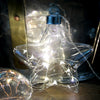Light up your world with some hanging glass lights. Add a beautiful twinkle to your home, perfect for living, ambience, or special occasions.  10 x warm white LED seed lights Clear Glass - Silver Wire 25cm hanging cord with on/off switch that doubles as a subtle battery pack Powered by CR2032 batteries, included