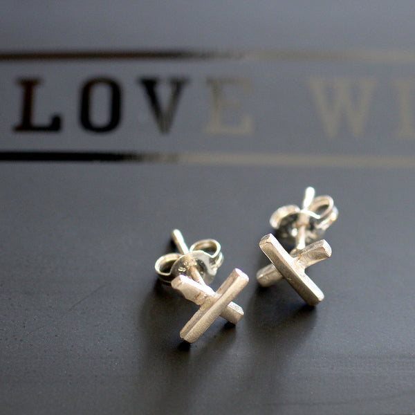 Cross Stud earrings Born out of a desire to create pretty pieces for everyday wear, Delwynne Winter is the creator and maker of Love Winter jewellery. Every one of her pieces is hand crafted, using 100% sterling silver, 9ct Gold, brass and copper, all made in her studio in Takapuna.  Size: • 8mm cross width • Sterling silver