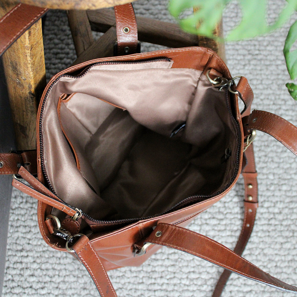 Genuine Leather Large Tan Tote  Antique Gold Buckle adjusting Handles  Detachable Cross Body Strap with Antique Gold Fittings  Rear Exterior Zip Closing Pocket  Zip with Leather Pull for Total Bag Closing  Single Internal Compartment with Zip closing pocket and two open pockets  Complimentary Lining  Size: 285 H x 365 W x 90 D mm
