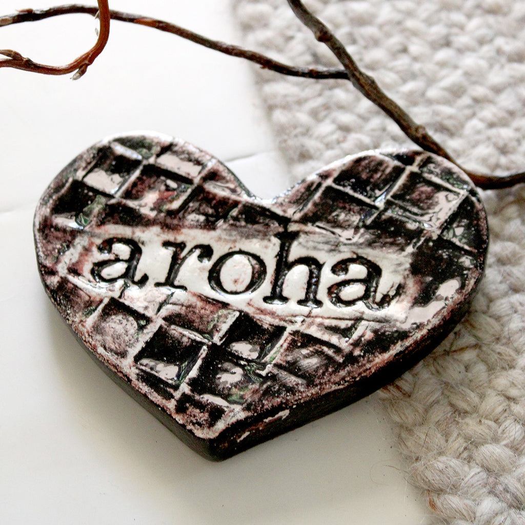 Aroha Heart tile Handmade in NZ!  Ceramic heart shape tile featuring an imprinted flax design and the word aroha.  Ideal for the wall or adorn any coffee table or bedside table in the house.  Size: 13 W x 11 H cm approx