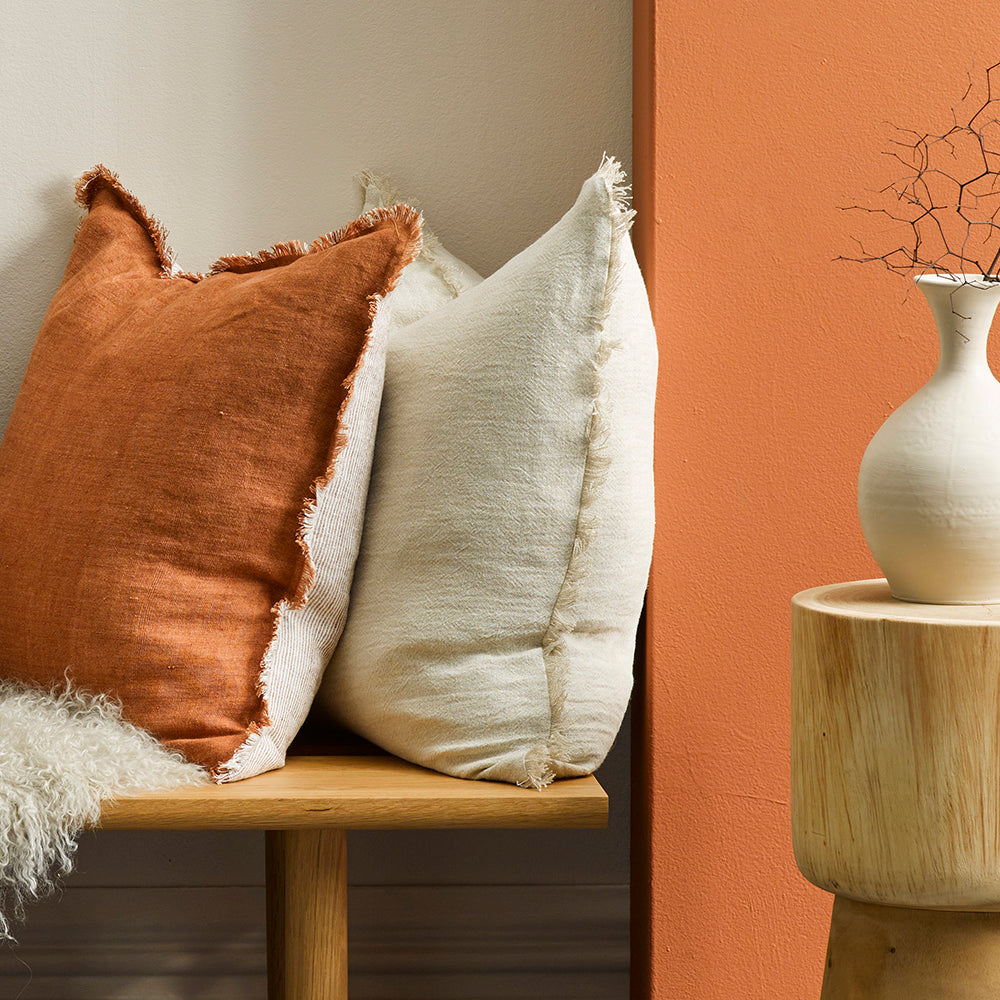 Mulberi Kendall Cushion is a versatile double-sided design that features a fine pinstripe on one side and a warm solid tobacco-rust tone on the other, handwoven in 100% linen. It's designed with a softly fringed edge to create a simplistic and homespun feel.  50x50cm Includes feather inner 100% linen