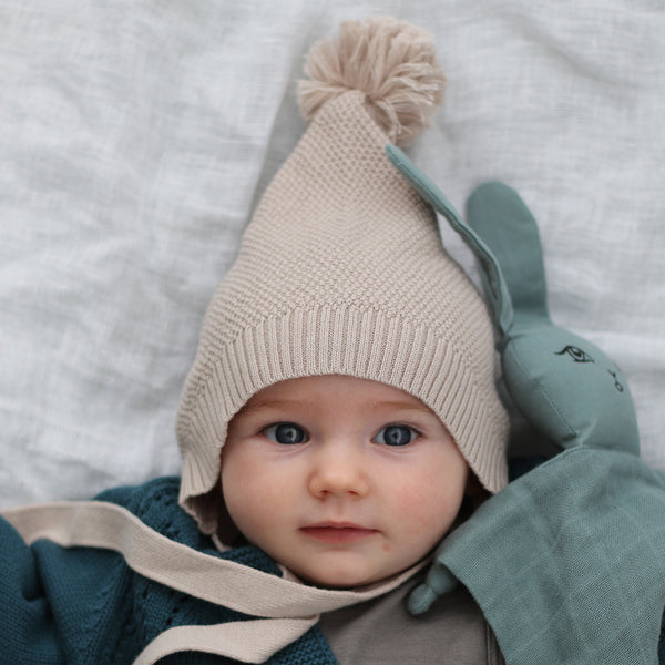 This sweet wee knit bonnet is a welcome new addition to the Collection. Made from 100% organic cotton knit, it features an adorable pom pom and an under the chin tie to keep it nice and snug.  It is lovely and soft (with no nasties) against delicate skin, and available in our gorgeous Pink and Oatmeal colourways. The perfect finishing touch for any baby's outfit over the cooler months!