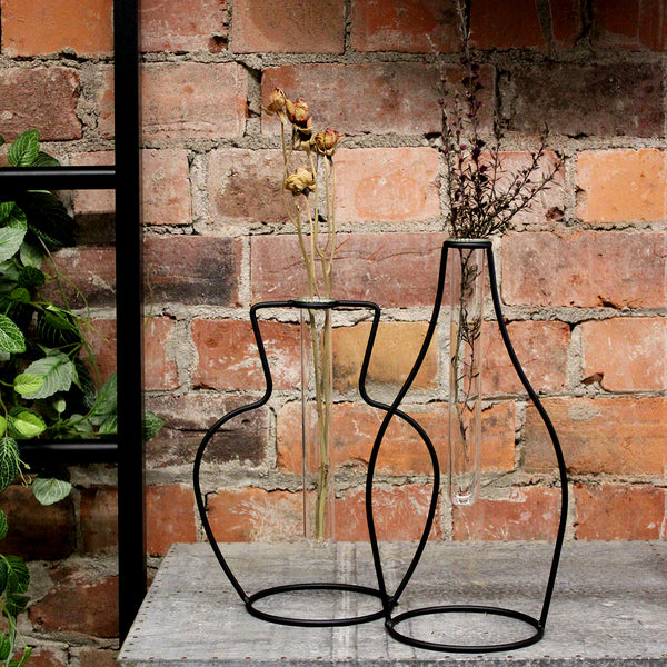 So simple but so effective. These metal frame test tubes vases look great paired together or on their own. The simple metal vase shaped frame holds one glass test tube. Perfect for a simple fresh bloom or your favourite dried arrangement.  Metal Frame Glass Test Tube  Style #1: w20 x d12 x h25cm Style #2 w15 x d12 x h30cm
