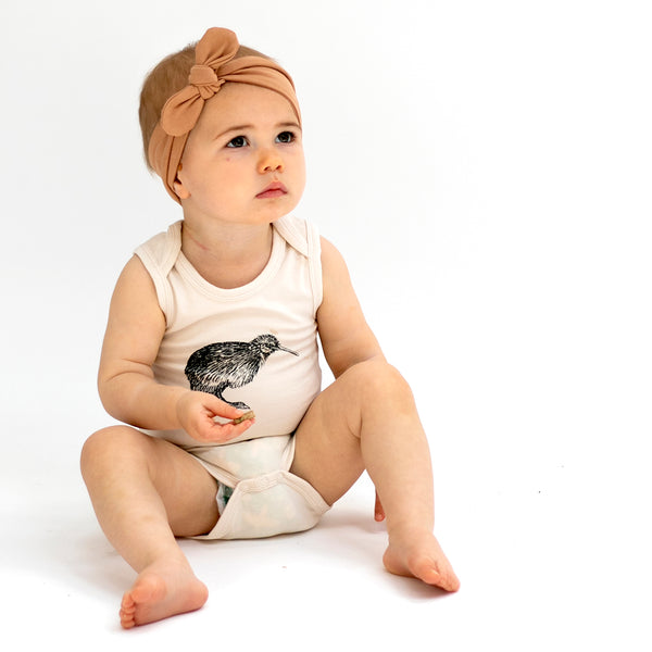 The Essentials singlet onesie, with an envelope neckline for easy dressing.  Made from 95% GOTS certified organic cotton 5%  elastane.  Available in a selection of colours and Prints  • Sizing from NB to size 1 • Designed in NZ  • Ethically made by our friends in India