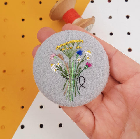 grey embroidered floral badge