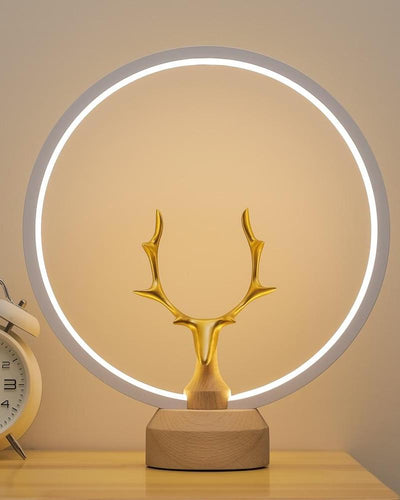 A light lamp with a golden deer, wooden base and a halo light on a night stand next to an alarm clock