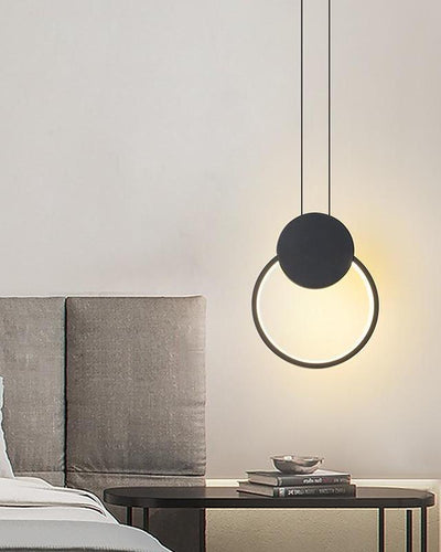 A circular, modern ceiling lamp hanging in a room over a desk
