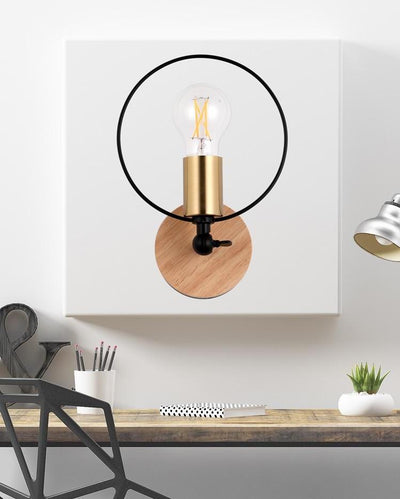 A cicular wall lamp with a wooden base and a black ring hanging on a white wall