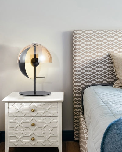 An architectural lamp with a half moon design on a night stand next to a bed
