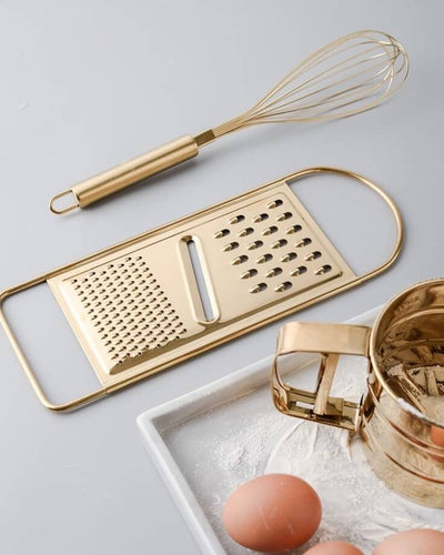 Golden egg beater made of stainless steel next to other golden kitchen utensils