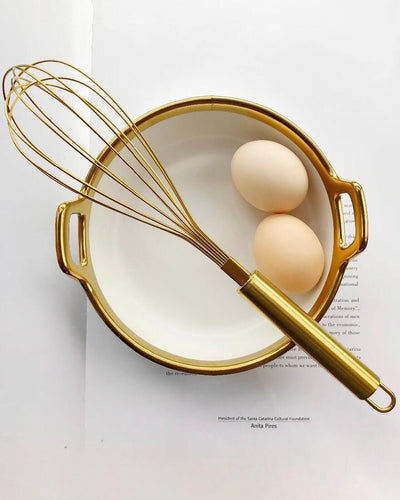 Egg beater in gold on a golden pot with 2 eggs