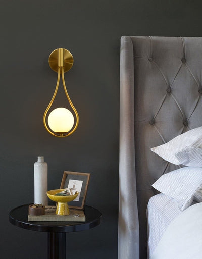 Golden wall lamp hanging in a bedroom next to a bed and a night desk