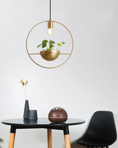 A golden ceiling lamp with a plant in it hanging over a black table and a black chair on white background