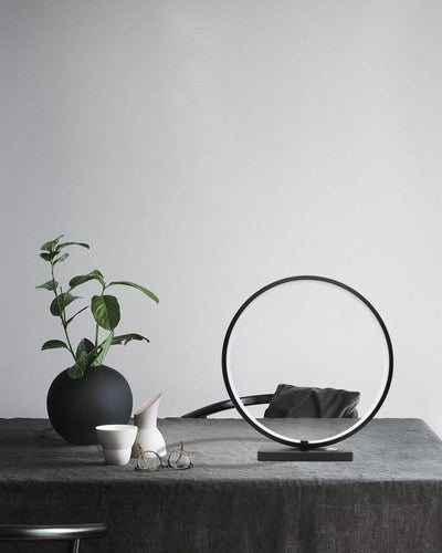 A circular desk lamp on a grey desk on white background