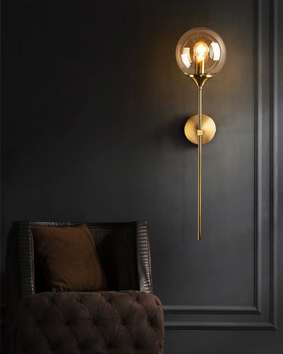 A nordic wall lamp with a long golden rod on a gray wall next to a brown couch