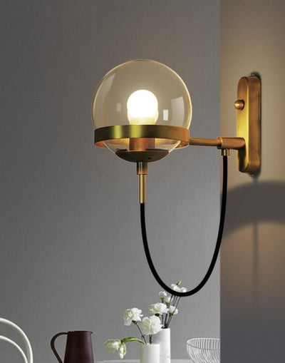 A nordic wall lamp made of bronze hanging on a grey wall next to white flowers