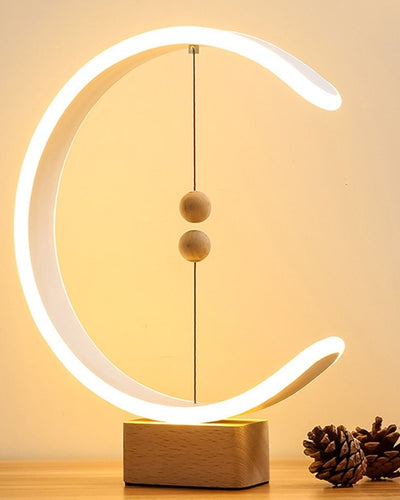 Magnetic Lamp with wooden base and two wooden spheres in a circular design and warm light