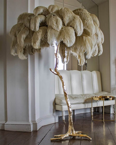 Tree lamp with a golden body and real ostrich feathers in grey in a white living room