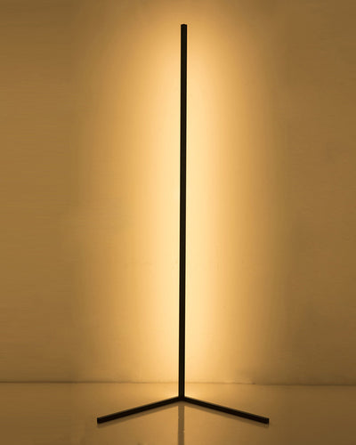 Geometric tripod floor lamp in black color with a long rod emitting warm light