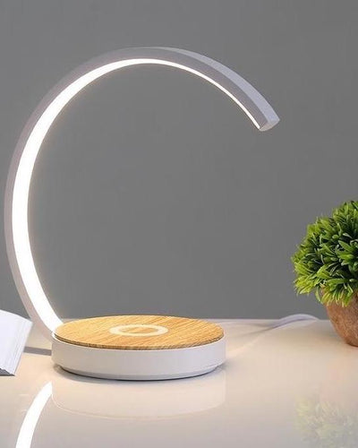 Wireless charging desk lamp made of wood in white color next to a plant on a desk