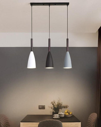 A triplet of ceiling lamps in white, black and grey color hanging on top of a wooden table