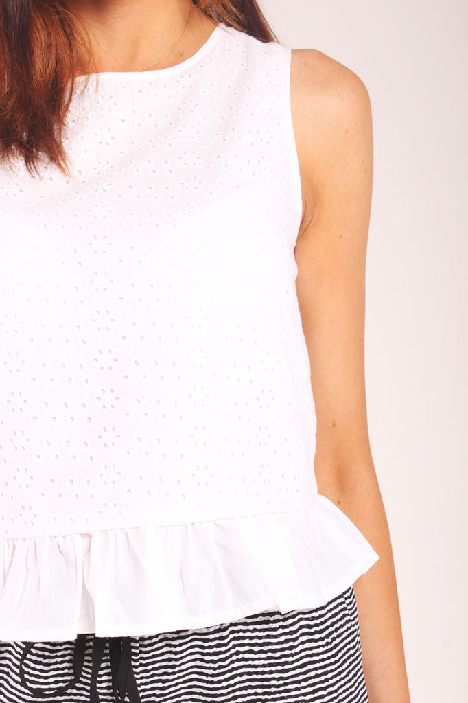 White sleeveless top in broderie anglaise and frilled hem