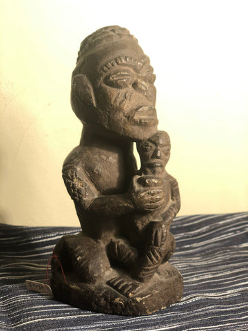 Ntadi grave marker   carved soapstone   Bacongo; Congo, PRC, West Africa  Seated figure with child    adult figure shows ritual scarification thruout body  conical headware. Nose of central figure ritually defaced.  collected in 1950's  dated late 19th/early 20th century