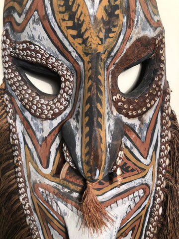 Papua New Guinea Sepik River mask. Carved and painted wood with cowrie shells set in clay and a boar tusk along the nose.