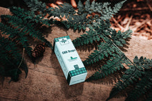 Load image into Gallery viewer, Green Jungle CBD Oil Drops Packaging Box On Wood Covered In Foliage