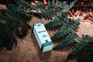 Green Jungle CBD Oil Drops Packaging Box On Wood Covered In Foliage