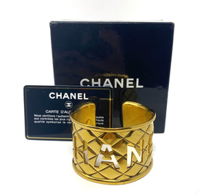 chanel gold bangle, quilted with logo cut-out, authenticity card.