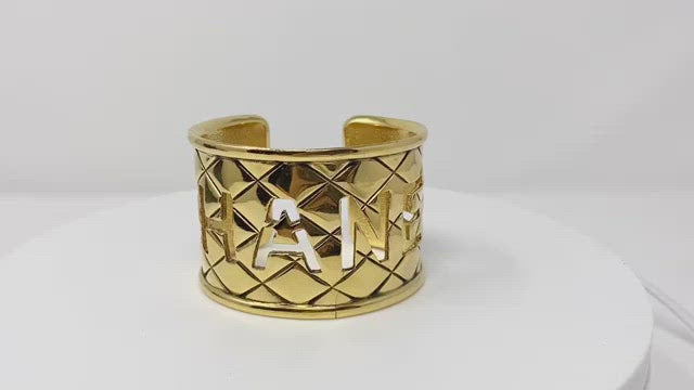 chanel gold bangle, quilted with logo cut-out.