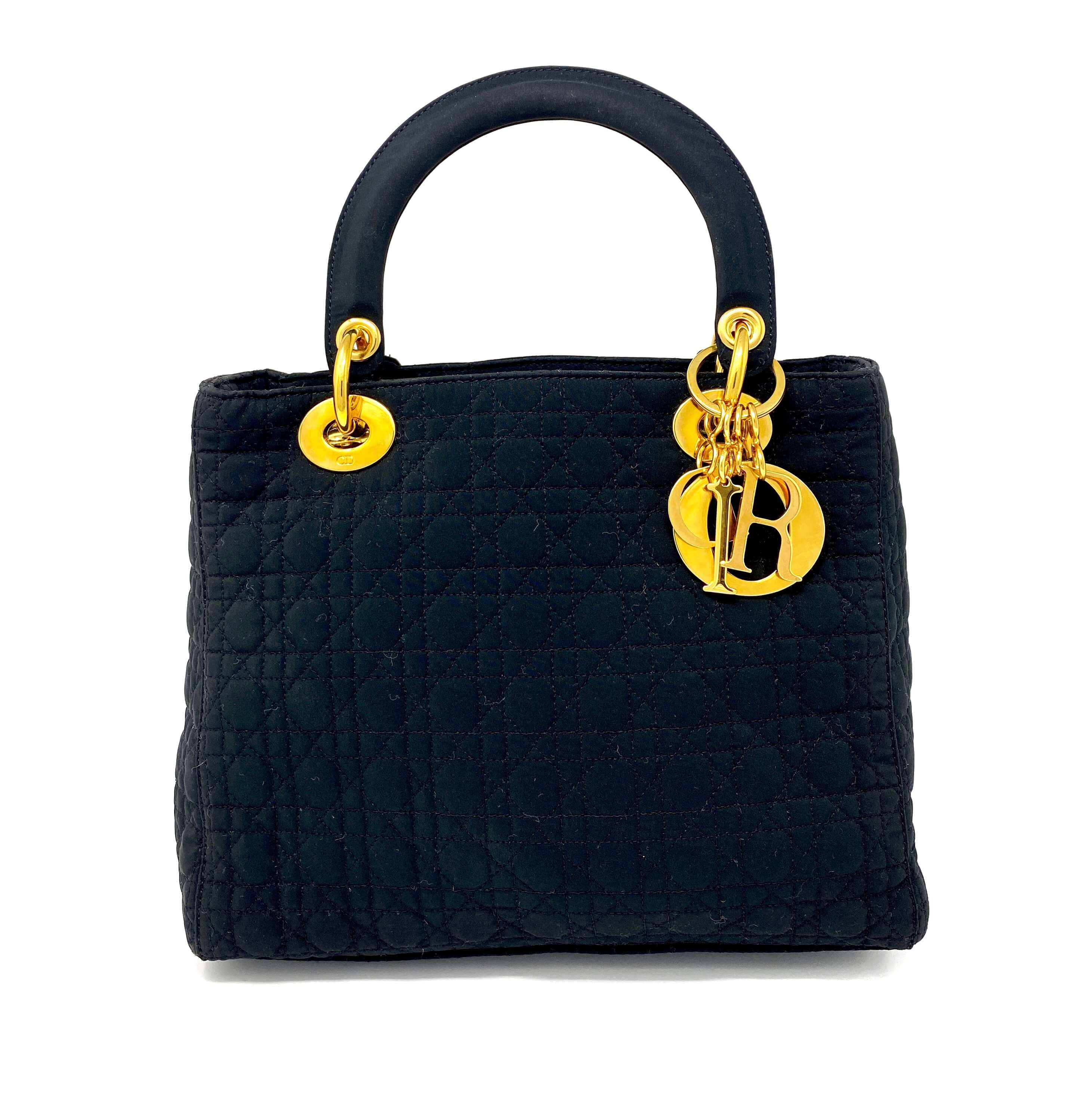 lady dior bag, black canvas, with Dior charms in gold.