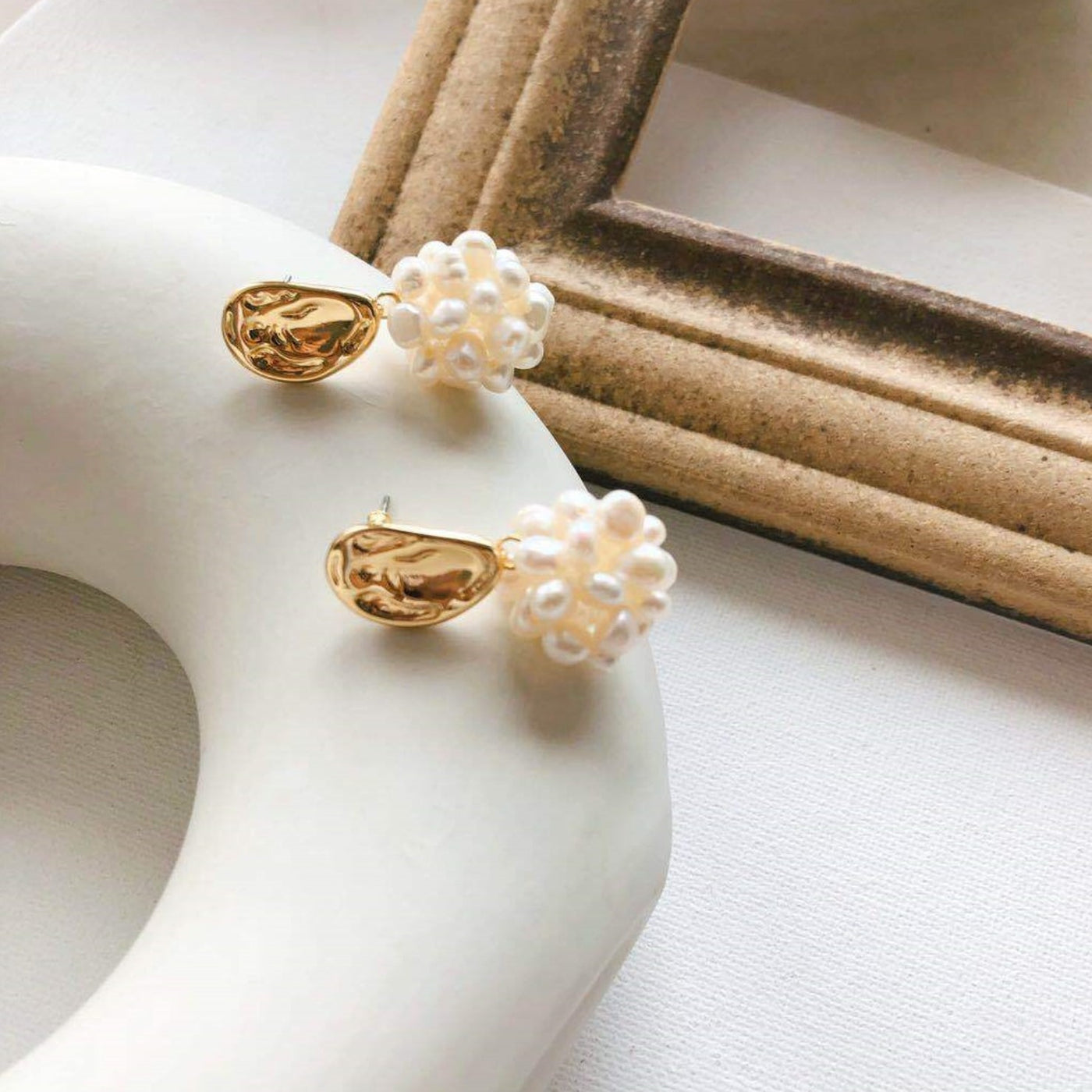Golden pearl drop earrings displayed on light background