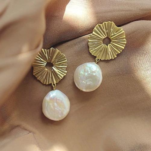 golden earrings in a sun dial shape with a baroque pearl suspended at the bottom displayed on brown background