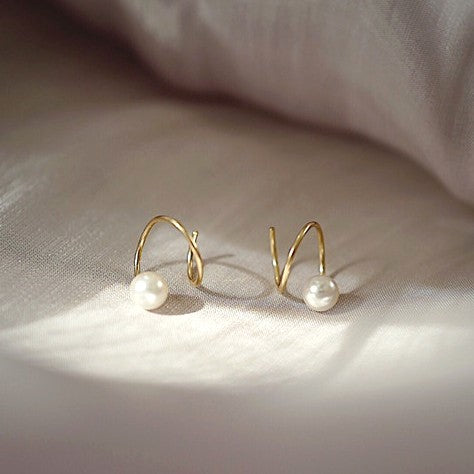 swirl golden earrings with a pearl displayed on grey background