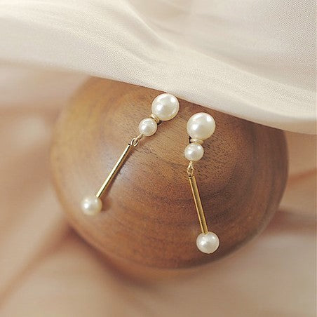 golden bar earrings with three pearl globes on two end displayed on wooden ball
