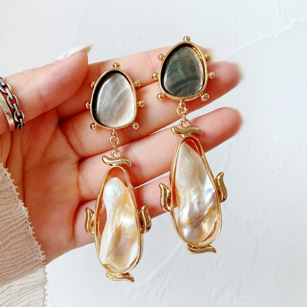 large baroque-pearls drop earrings suspend from mother-of-pearl plates with gold accents displayed on hand