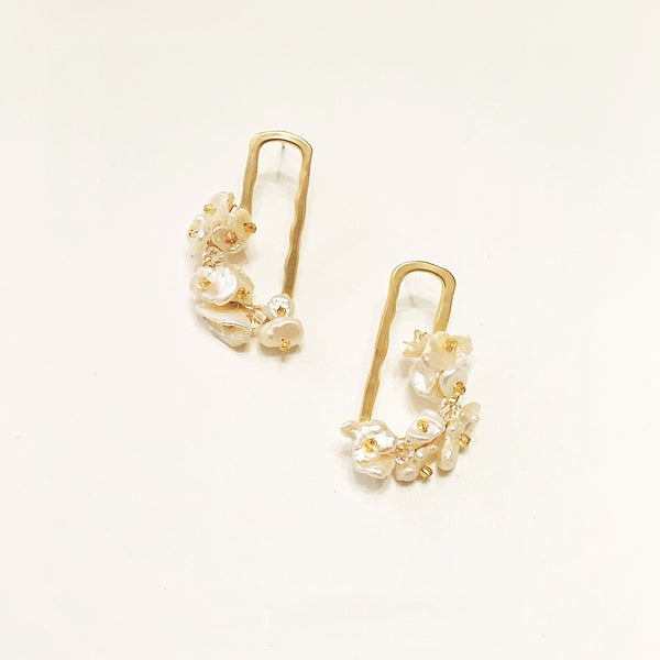 gold rectangular drop earrings with baroque pearl flowers displayed on beige background