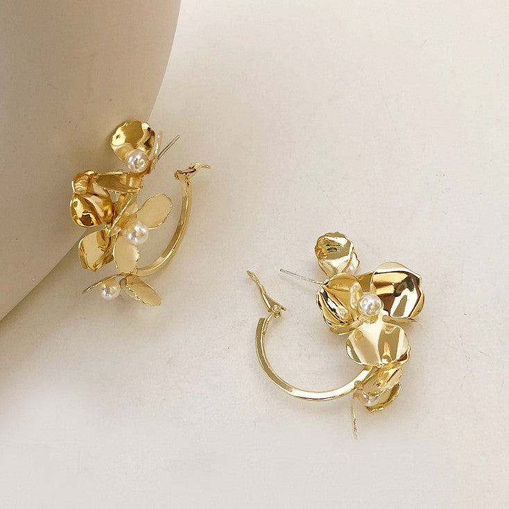 golden flower hoop earrings displayed on beige background